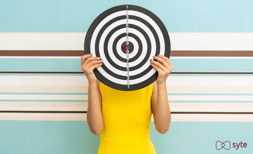 A woman holds up a target represented targeted advertising.