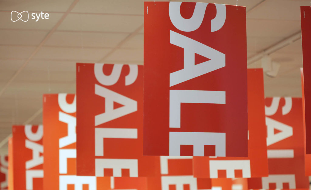 sale signs hang from ceiling in a retail store